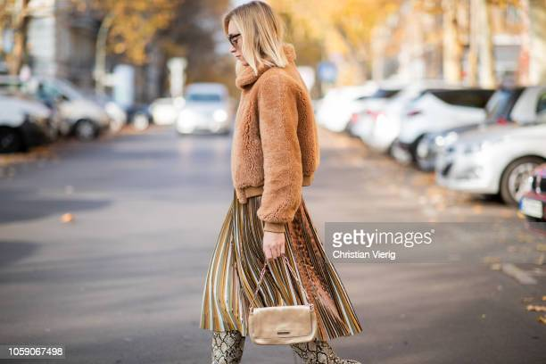 Sonia Lyson is seen wearing snake boots Zara pleated skirt Max Co turtleneck Zara brown shearling jacket Ducie golden vintage bag Gucci Dior...