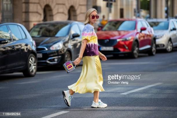 Sonia Lyson is seen wearing sneaker Adidas, yellow satin skirt Zara, batik shirt Zara, Boyy bag, Wald Berlin jewellery, Dior sunglasses during...