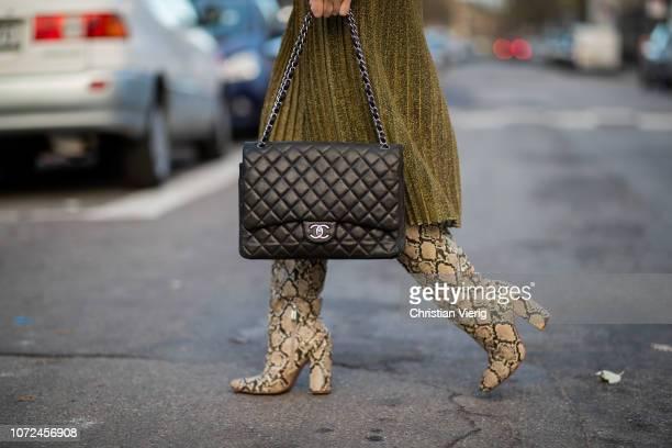 Sonia Lyson is seen wearing turquoise knit midi pleated skirt Samsoe Samsoe Zara snake print boots Chanel bag red sunglasses Jimmy eyewear on...
