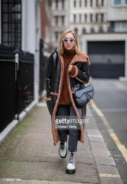 Sonia Lyson is seen wearing white Dr Martens boots Levis jeans rust colored Zara turtleneck knit black Dior saddle bag Vogue eyewear x Gigi Hadid...