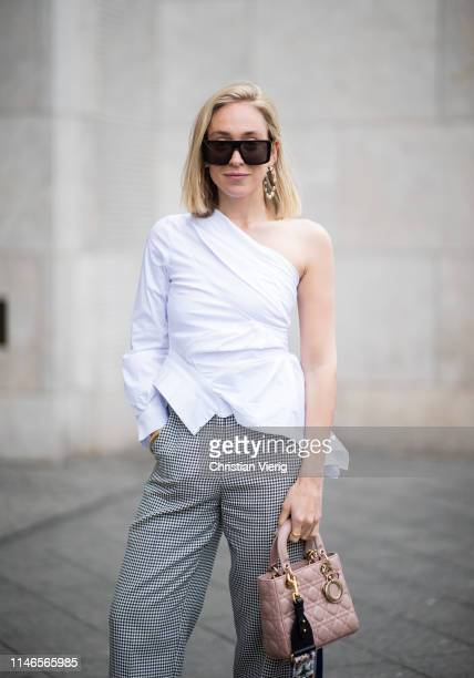 Sonia Lyson is seen wearing white ripped off top, Dior bag, grey pants on May 02, 2019 in Berlin, Germany.