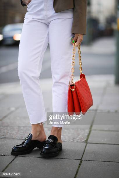 Sonia Lyson poses wearing beige Zara blazer and white jeans, black Prada loafers and red Louis Vuitton leather bag on March 22, 2021 in Berlin,...