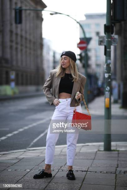 Sonia Lyson poses wearing black Zara top, white jeans and beige blazer, Prada hat, earring and black loafers and red Louis Vuitton leather bag on...