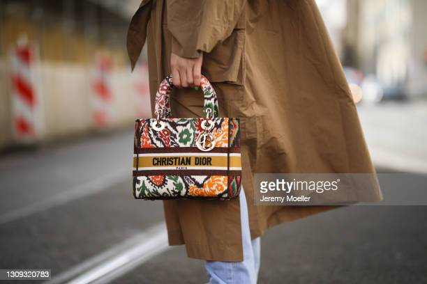 Sonia Lyson poses wearing blue Zara jeans, Rabens Saloner trenchcoat and Lady Dior bag on March 22, 2021 in Berlin, Germany.