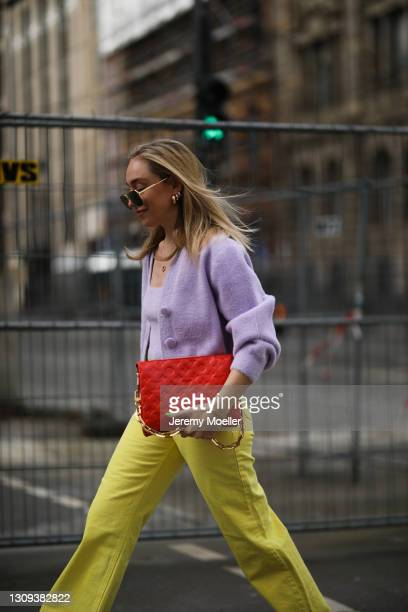 Sonia Lyson poses wearing lilac & other stories top and cardigan, shades, yellow Zara pants and red Louis Vuitton leather bag on March 22, 2021 in...