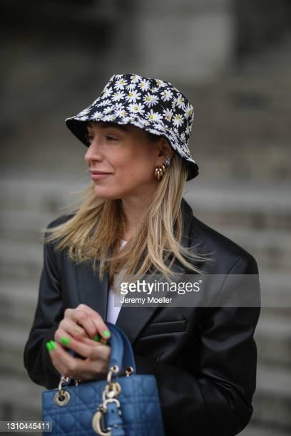 Sonia Lyson poses wearing Pull & Bear flower bucket hat, black Zara blazer and Lady Dior bag on March 29, 2021 in Berlin, Germany.