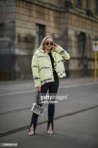 Sonia Lyson poses wearing yellow Rabens Saloner tie dye jacket, dark grey Arma pants, sparkling Zara heels and grey Dior Caro bag on March 22, 2021...