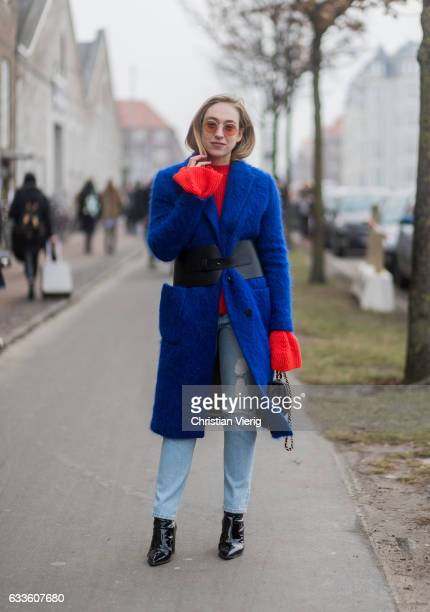 Sonia Lyson wearing a blue coat with belt denim jeans red knit outside By Malene Birger during the Copenhagen Fashion Week Autumn/Winter 17 on...