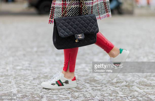 Sonia Lyson wearing a checked coat Carven black Chanel bag red PVC pants Topshop Gucci sneaker Miu Miu sunglasses Ivy Revel knit during the...
