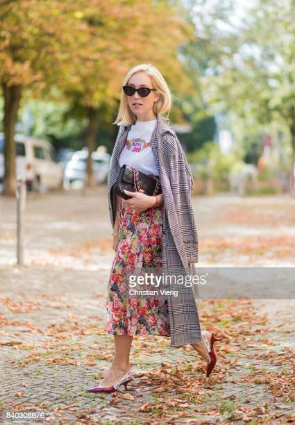 Sonia Lyson wearing a midi skirt with floral print Ganni a white Tshirt with the print Love Dog from Ganni a black Chanel vintage bag vintage...