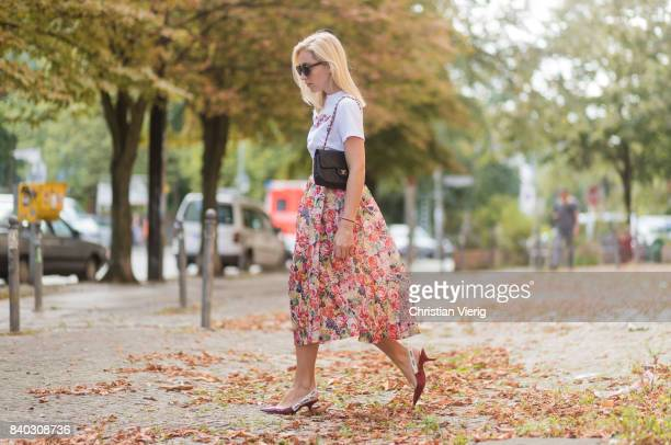 Sonia Lyson wearing a midi skirt with floral print Ganni, a white T-shirt with the print Love Dog from Ganni, a black Chanel vintage bag, vintage...