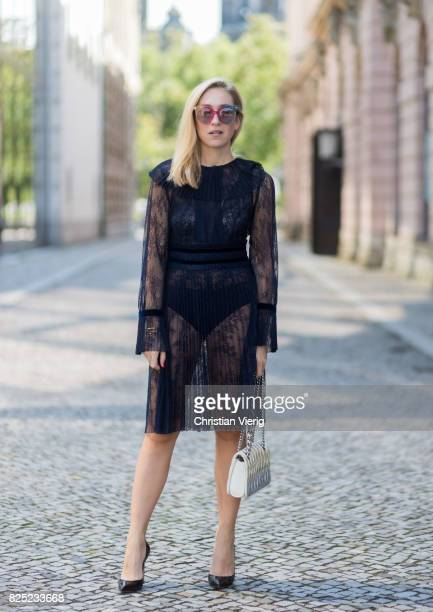 Sonia Lyson wearing a navy sheer cocktail party dress with long sleeves from Tara Jarmon a silver Miu Miu bag MCM sunglasses black Gianvito Rossi...