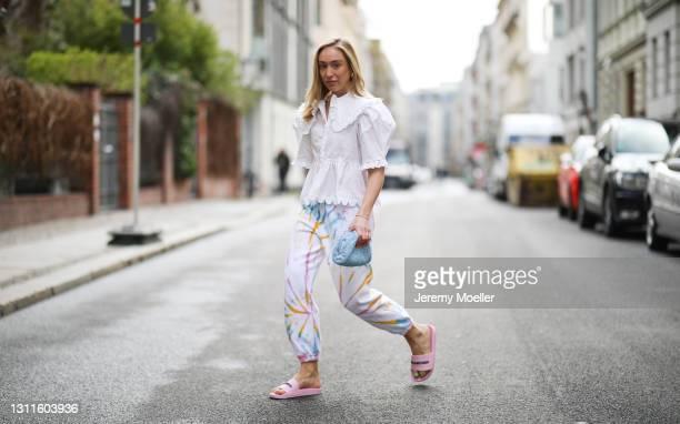 Sonia Lyson wearing baby blue Bottega Veneta mini pouch, pink Balenciaga sandals, Sprwmn Los Angeles tie dye sweatpants and white horror vacui blouse...