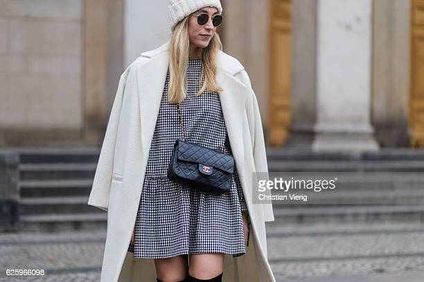 Sonia Lyson wearing black overknees boots Stuart Weitzman a grey white checked plaid dress Zara a white wool coat Lala Berlin a white wool hat other...