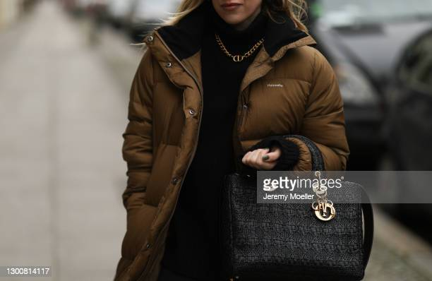 Sonia Lyson wearing brown Holzweiler coat, Dior chain and black bag and H&M sweater on February 05, 2021 in Berlin, Germany.