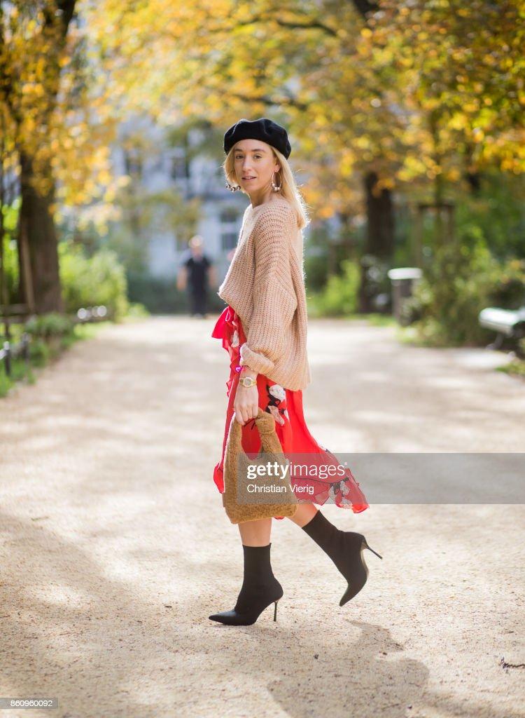 Sonia Lyson wearing brown Loeffler Randall teddy fake fur bag, red ruffled skirt Gannix x Anita Hass, oversized cashmere sweater Zara, black sock boots Zara, black beret Urban Outfitters, earrings Topshop on October 13, 2017 in Berlin, Germany.