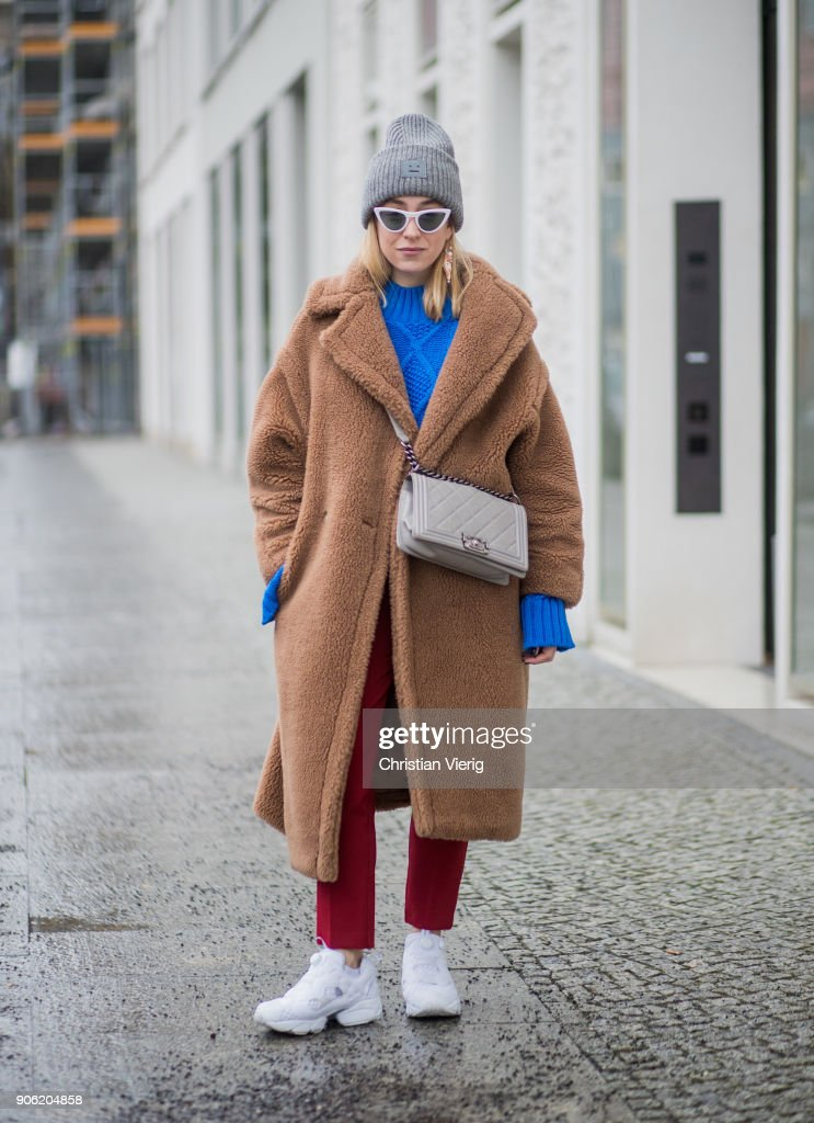 Sonia Lyson wearing brown teddy coat Max Mara, red pants, blue cropped jumper Topshop, white sneaker Reebok, grey Chanel bag, Gucci belt, Acne beanie, white sunglasses is seen during the Berlin Fashion Week January 2018 on January 17, 2018 in Berlin, Germany.
