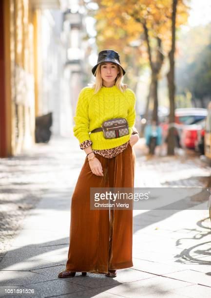 Sonia Lyson wearing brown wide leg velvet pants neon jumper leopard print blouse Samsoe Samsoe boots Topshop Gucci bag bucket hat on October 11 2018...