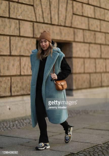 Sonia Lyson wearing Chanel sneaker, black Sporty & Rich sweater, Zara black pants, Max Mara baby blue Teddy vest, Dior Bobby bag and Andiata beige...