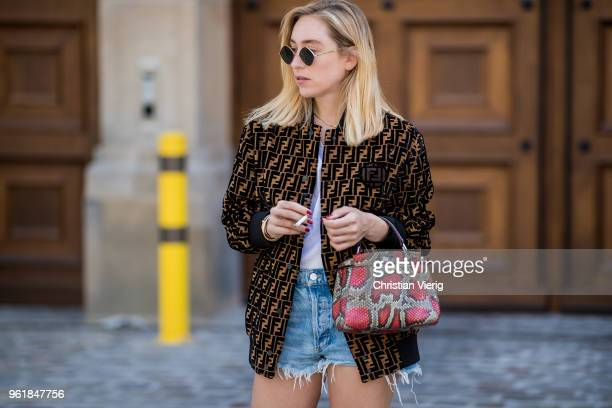 Sonia Lyson wearing denim cut off shorts rgolde Fendi bomber jacket ff reloaded Topshop sunglasses Fendi bag on May 23 2018 in Berlin Germany