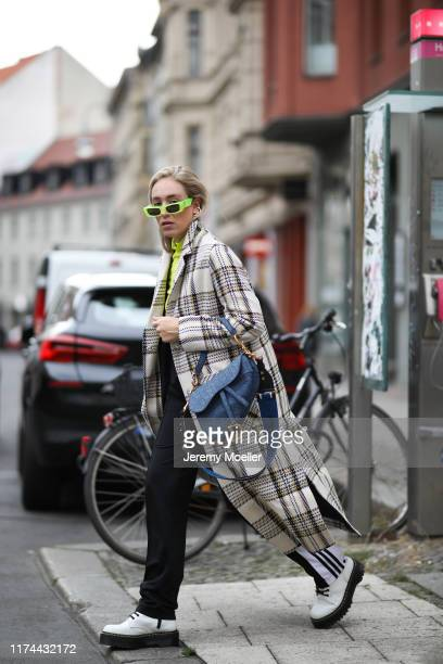 Sonia Lyson wearing Dior saddle bag Dr Martens Jadon boots Adidas track pants Edited coat Edited top and Gucci sunglasses on September 13 2019 in...