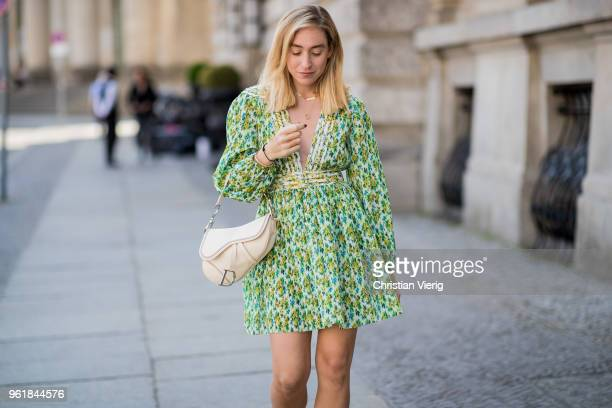 Sonia Lyson wearing green Zimmermann dress with floral print, Jimmy Choo heeled sandals, Dior settle bag on May 23, 2018 in Berlin, Germany.