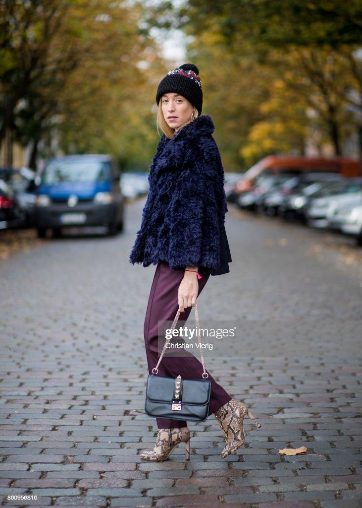 Sonia Lyson wearing Jimmy Choo boots with snake skin print, navy fake fur cropped jacket Nobi Talai, bordeaux pleated trousers Nobi Talai, wool beanie Lala Berlin, black bag Valentino on October 13, 2017 in Berlin, Germany.