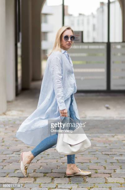 Sonia Lyson wearing Kurt Geiger shoes with lobster print a blue oversized button shirt and denim jeans Zara a vintage bag Topshop hoop earings erdem...