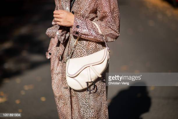 Sonia Lyson wearing leo print coat Munthe Dior saddle bag in creme Ganni cowboy boots sunglasses on October 11 2018 in Berlin Germany