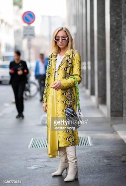 Sonia Lyson wearing long silk skirt and yellow snake print coat white boots Zara sunglasses Mango Balenciaga fanny bag is seen during Milan Fashion...