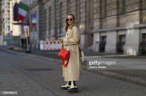 Sonia Lyson wearing Louis Vuitton Coussin red bag, Jimmy Choo shades, Bottega Veneta beige boots and Edited jogging suit and beige coat on February...