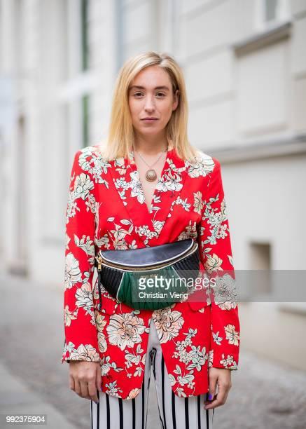 Sonia Lyson wearing Miu Miu belt bag Manolo Blahnik heels red blazer with floral print shell necklace Wald Berlin white black striped pants Topshop...