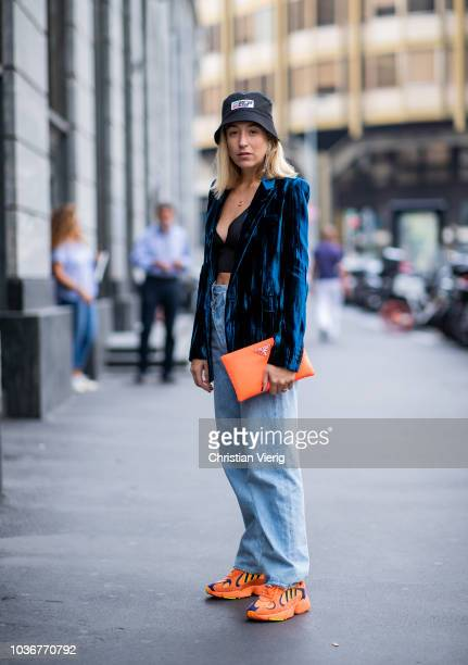 Sonia Lyson wearing orange Adidas sneaker fisher hat Prada asymmetric jeans Agolde bustier Zara velvet blazer YSL orange clutch Prada is seen during...