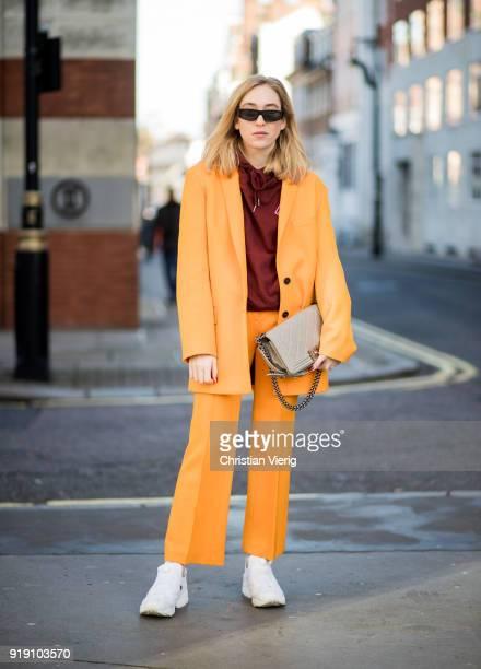 Sonia Lyson wearing orange Lala Berlin suit Reebok pump sneaker grey Chaenl boy bag tiny sunglasses Zara seen during London Fashion Week February...