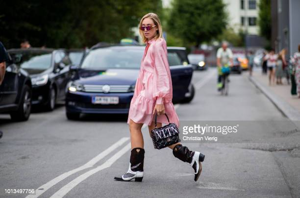 Sonia Lyson wearing pink dress, Valentino bag, boots is seen outside Stine Goya during the Copenhagen Fashion Week Spring/Summer 2019 on August 8,...