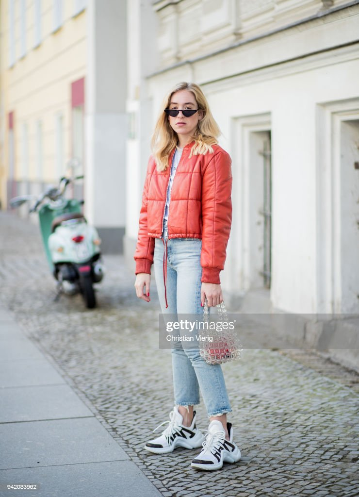 Sonia Lyson wearing red cropped bomber leather jacket Mango, Agolde denim jeans, white Louis Vuitton sneakers, transparent see through pearl bag Mango, mini sunglasses Mango is seen on April 4, 2018 in Berlin, Germany.