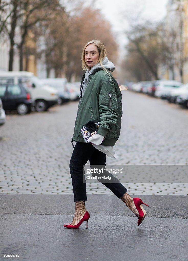 Sonia Lyson (@soniafrancex / PR Manager) wearing red heel pumps manolo blahnik, black cropped denim jeans Zara, grey hoody weekday white blouse weekday, khaki bomber jacket weekday, white Furla bag, black net tights falke on November 26, 2016 in Berlin, Germany.