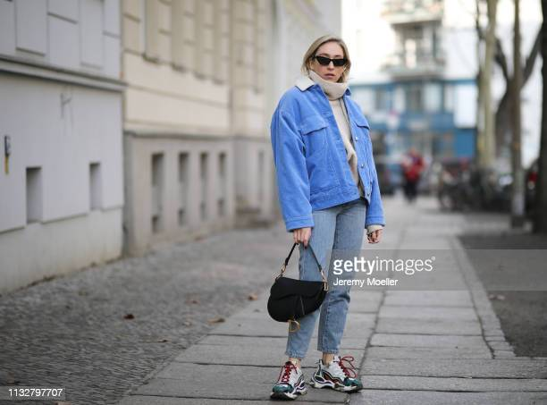 Sonia Lyson wearing Sandro shoes, Closed jeans, H&M sweater, Samsoe Samsoe jacket, Chimy eyewear, Dior bag on February 28, 2019 in Berlin, Germany.