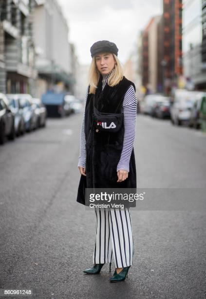 Sonia Lyson wearing shoes Jimmy Choo black white striped pants Topshop cropped turtleneck Longchamp black long fake fur vest Lala Berlin cap Zara...