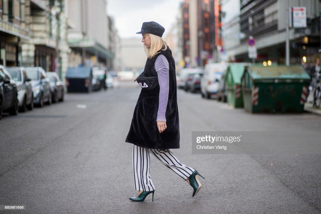 Sonia Lyson wearing shoes Jimmy Choo, black white striped pants Topshop, cropped turtleneck Longchamp, black long fake fur vest Lala Berlin, cap Zara, black belt bag Fila on October 13, 2017 in Berlin, Germany.