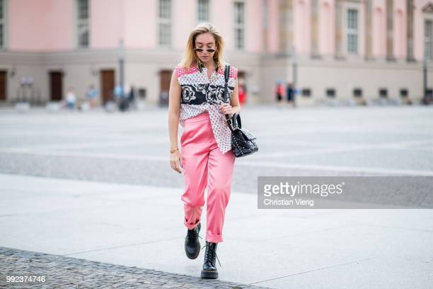 Sonia Lyson wearing sleeveless print blouse Prada pink pants other stories Dr Martens boots mini sunnies Asos bag Valentino Rockstud is seen during...