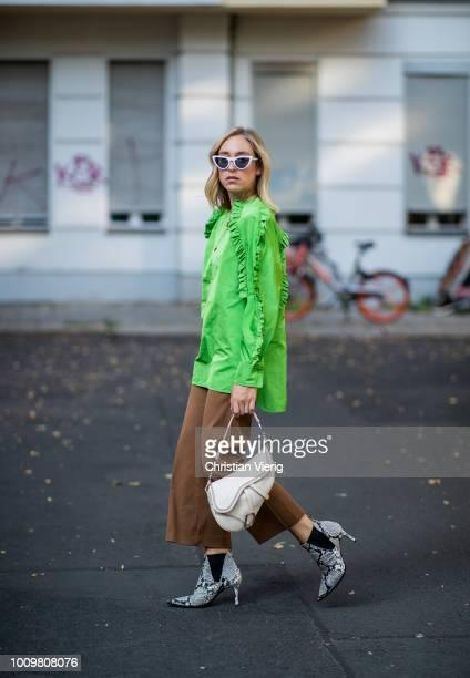 Sonia Lyson wearing snake print ankle boots Zara brown cropped pants Zara Dior saddle bag green Escada ruffled top Vogue eyewear x Gigi Hadid...