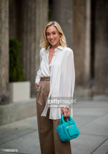 Sonia Lyson wearing white blouse, brown striped pants, turquoise bag outside Max Mara Resort 2020 on June 03, 2019 in Berlin, Germany.