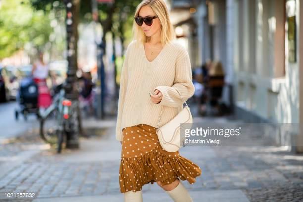 Sonia Lyson wearing white boots Zara Baum und Pferdgarten skirt Acne knit Celine sunglasses Dior saddle bag on August 22 2018 in Berlin Germany