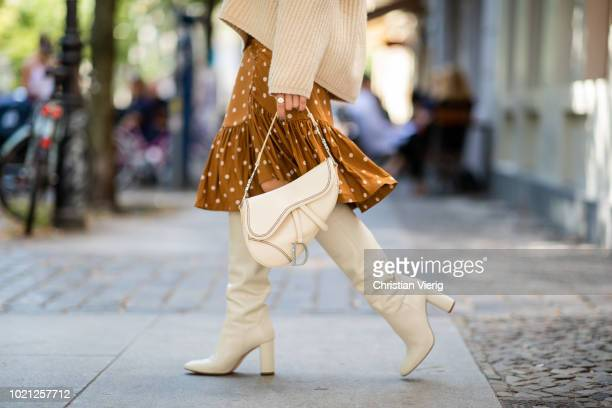Sonia Lyson wearing white boots Zara Baum und Pferdgarten skirt Acne knit Celine sunglasses Dior saddle bag on August 22 2018 in Berlin Germany