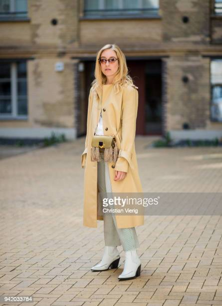 Sonia Lyson wearing white cowboy boots Mango cropped flared striped pants and white tshirt Edited trench coat Topshop olive Jimmy Choo lockett mini...