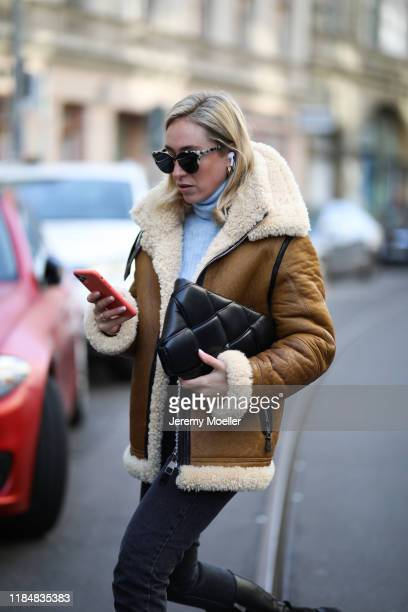 Sonia Lyson wearing Zara jeans and sweater, Ducie jacket, Bottega Veneta bag and Dior sunglasses on October 31, 2019 in Berlin, Germany.