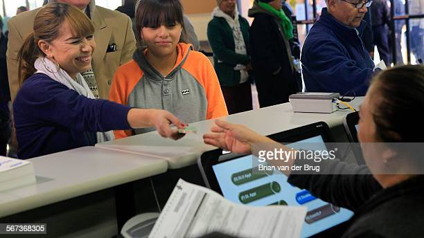 Sonia Soriano left with daughter Kelya right was first in line to fill out paperwork for her California driver license at DMV offices January 2 2015...
