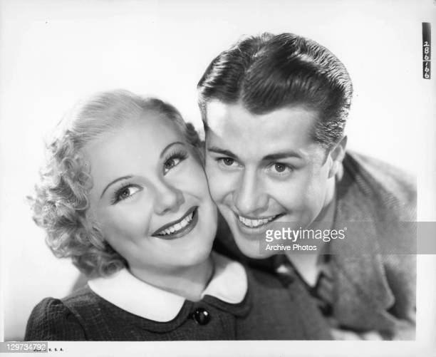 Sonja Henie and Don Ameche smiling together in a scene from the film 'Happy Landing' 1938