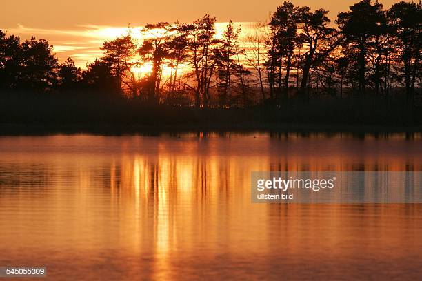 Sonnenuntergang am Wasser mit bewaldeter Insel am VaenernSee in Schweden groesster See Skandinaviens